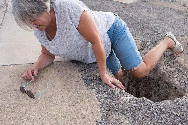Mulher madura ou sênior caminhando em uma zona de construção e caindo em um grande buraco com a perna dentro dele - precisando de ajuda no chão com dor