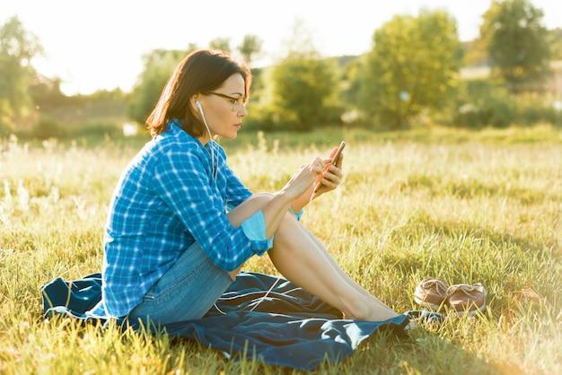 Mulher madura ouve música, um audiolivro em fones de ouvido, relaxa na natureza