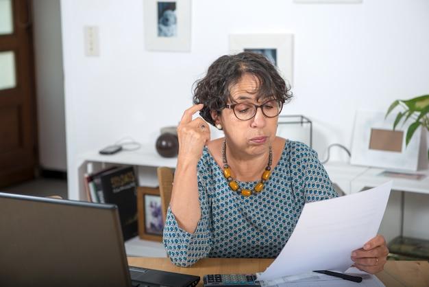 Mulher madura pagando contas e tendo um problema
