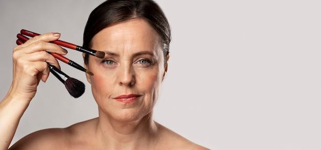 Mulher madura posando com pincéis de maquiagem e espaço de cópia