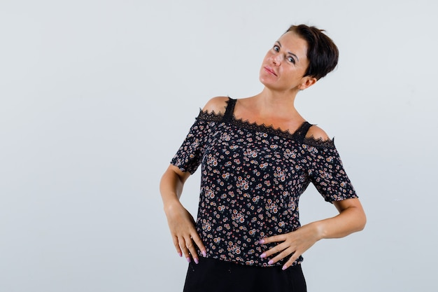 Mulher madura posando, mantendo as mãos na cintura na blusa e olhando pensativa, vista frontal.