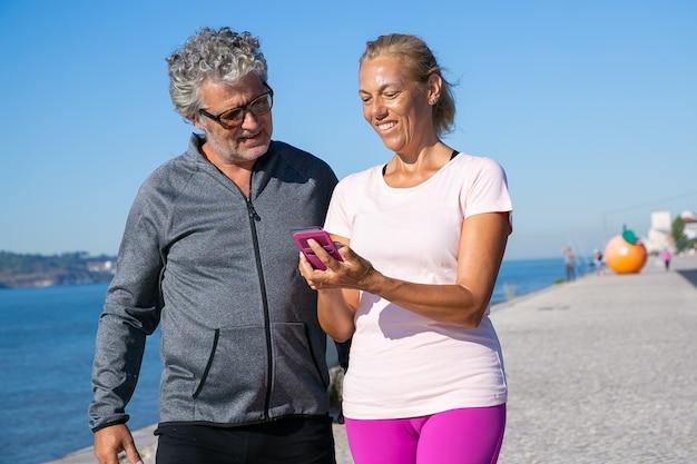 Mulher madura positiva usando o aplicativo de fitness no celular depois de correr, mostrando a tela para o homem. comunicação e gadget para o conceito de esporte