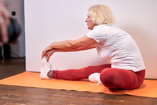 Mulher madura pratica esportes em casa no chão, linda mulher saudável esticando braços e pernas, pratica ioga, leva estilo de vida saudável