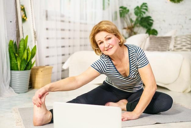 Mulher madura pratica esportes olhando para o monitor online home fitness
