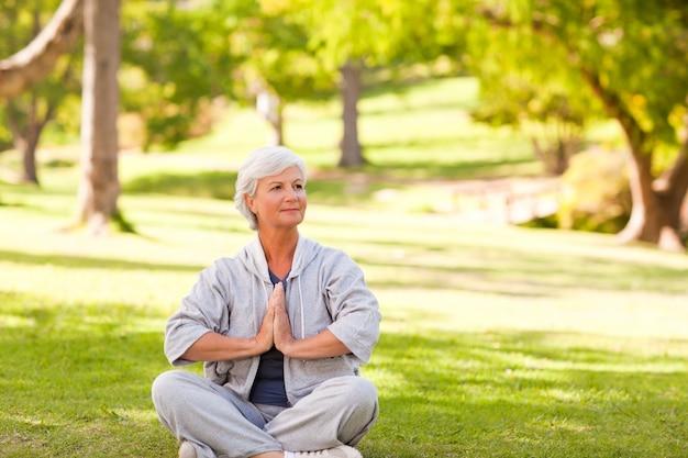 Mulher madura praticando yoga no parque