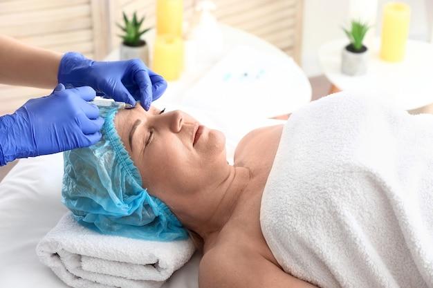Mulher madura recebendo injeção de preenchimento em salão de beleza