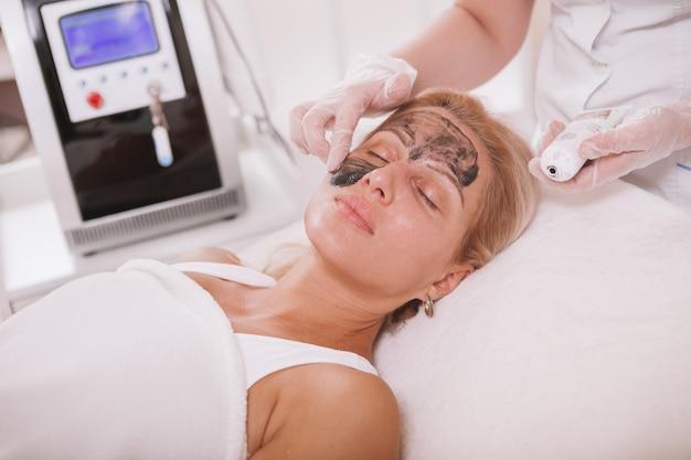 Mulher madura, recebendo tratamento de skincare facial no salão de beleza