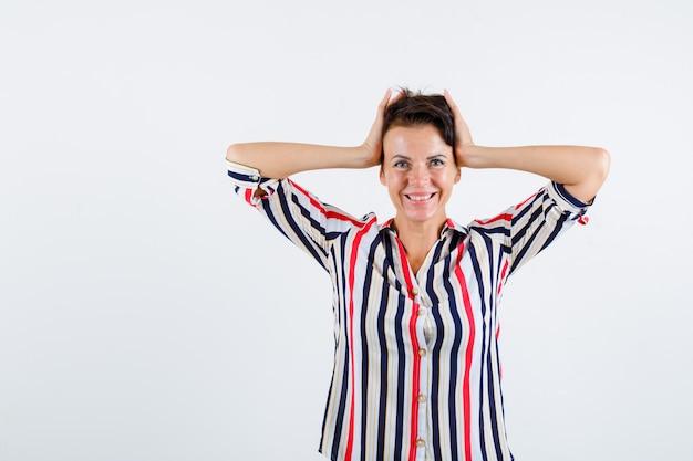 Mulher madura, segurando a cabeça com as mãos na camisa listrada e olhando feliz, vista frontal.