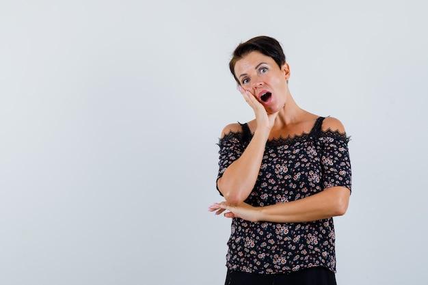 Mulher madura segurando a mão na bochecha na blusa e olhando perplexa, vista frontal.