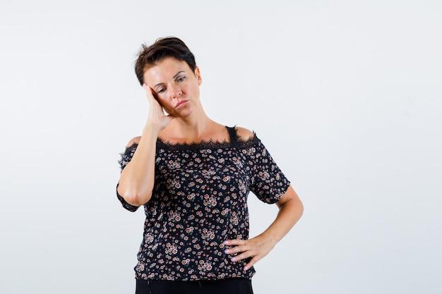 Mulher madura segurando a mão na cintura, apoiando a bochecha na palma da mão, olhando para baixo em uma blusa floral, saia preta e parecendo pensativa. vista frontal.