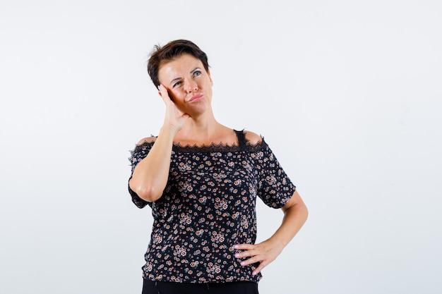Mulher madura segurando a mão na cintura, apoiando a bochecha na palma da mão, olhando para longe em uma blusa floral, saia preta e parecendo pensativa. vista frontal.