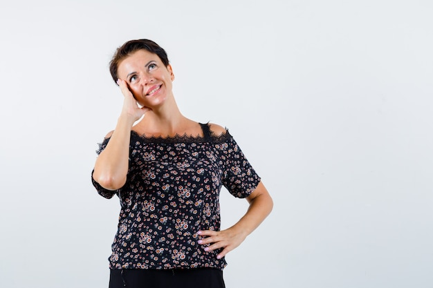 Mulher madura segurando a mão na cintura, apoiando a bochecha na palma da mão, sorrindo em uma blusa floral, saia preta e olhando pensativa. vista frontal.