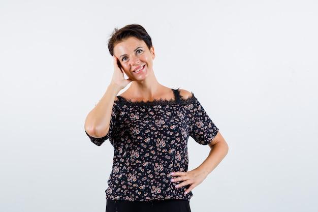 Mulher madura segurando a mão na cintura, apoiando a bochecha na palma da mão, sorrindo em uma blusa floral, saia preta e parecendo feliz. vista frontal.