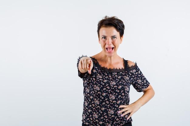 Mulher madura segurando a mão na cintura, apontando para a câmera, mantendo a boca aberta em uma blusa floral, saia preta e olhando alegre. vista frontal.