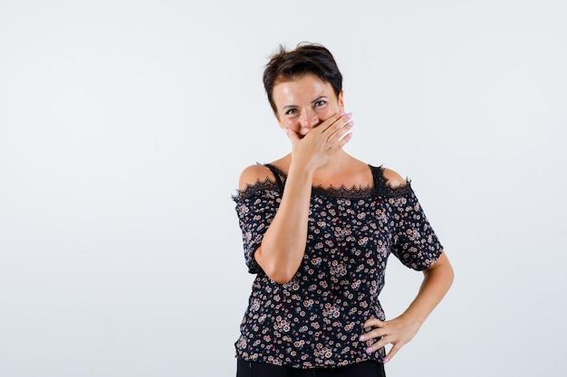 Mulher madura segurando a mão na cintura, cobrindo a boca com a mão na blusa floral, saia preta e parecendo alegre. vista frontal.
