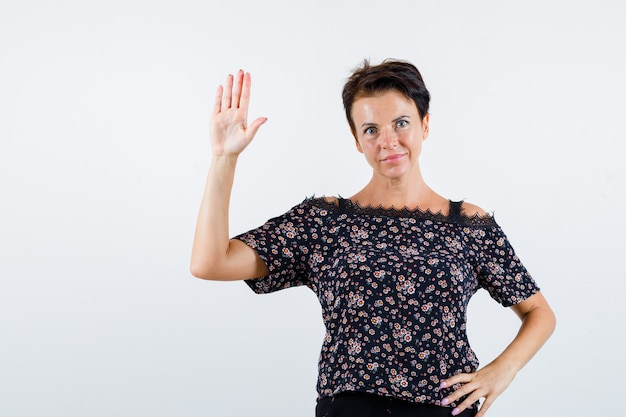 Mulher madura segurando a mão na cintura, mostrando o sinal de pare na blusa floral, saia preta e parecendo confiante. vista frontal.