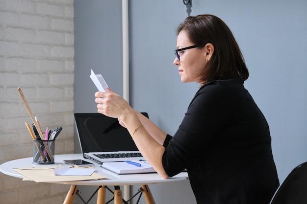 Mulher madura segurando papéis de negócios em mãos, documentos recebidos em envelopes pelo correio, no laptop de mesa, telefone, diário
