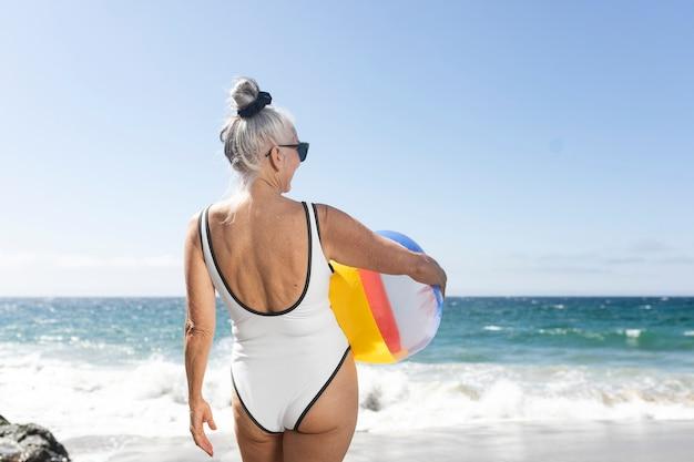 Mulher madura segurando uma bola de praia enquanto usa um maiô
