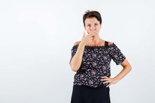 Mulher madura segurando uma mão na cintura, cobrindo a boca com a mão em uma blusa floral e saia preta e olhando séria, vista frontal.