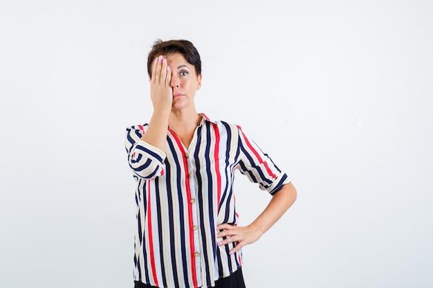 Mulher madura, segurando uma mão na cintura, cobrindo os olhos com a mão em uma camisa listrada e olhando séria, vista frontal.