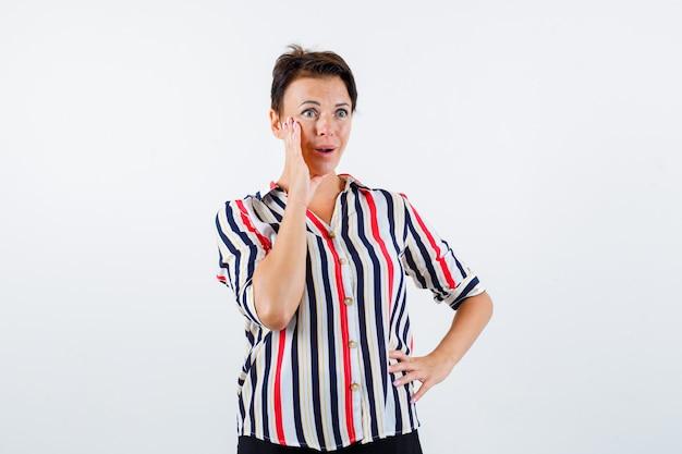 Mulher madura segurando uma mão na cintura, mantendo a outra mão perto da boca, chamando em uma camisa listrada e parecendo surpresa. vista frontal. Foto gratuita