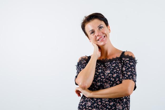 Mulher madura segurando uma mão no pescoço, a outra mão atrás do cotovelo em uma blusa floral, saia preta e parecendo alegre. vista frontal.