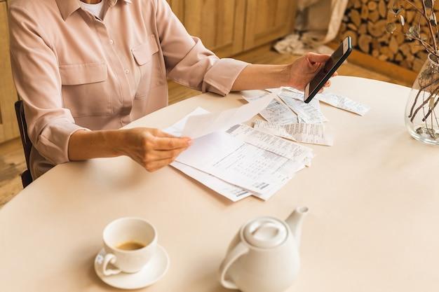 Mulher madura sênior de meia idade segurando uma nota de papel ou carta em casa para fazer pagamentos on-line no site no celular, calcular o custo da taxa de impostos financeiros, revisar a conta bancária.