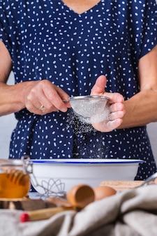Mulher madura sênior feliz, avó cozinhando, amassando massa, assando torta, bolo, biscoitos. atividade de outono em casa, em uma cozinha aconchegante.