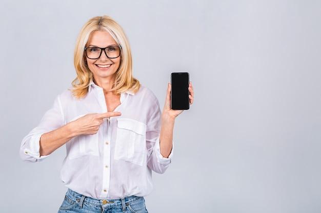 Mulher madura sênior feliz surpresa sorridente em casual mostrando a tela em branco do smartphone enquanto olha para a câmera isolada sobre um fundo cinza branco. usando o telefone.