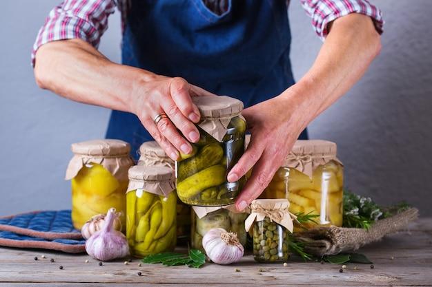 Mulher madura sênior segurando na jarra de mãos com comida caseira conservada e fermentada. variedade de legumes em conserva e marinados. limpeza, economia doméstica, preservação da colheita