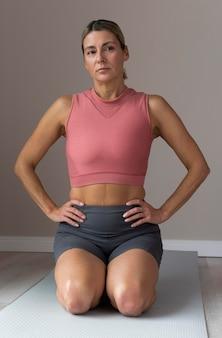 Mulher madura sentada em um tapete de ioga de frente