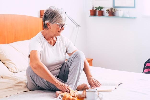 Mulher madura sentada na cama lendo um livro e comendo croissant e crocantes e bebendo suco de laranja - sênior aposentada tomando café da manhã isolado e sozinho pela manhã