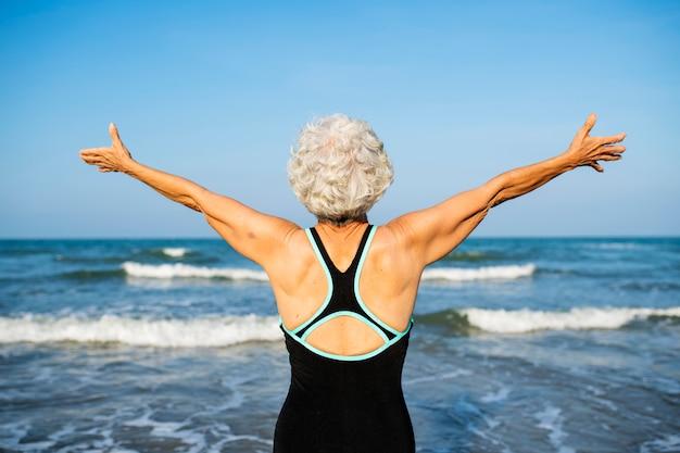 Mulher madura, sentindo-se livre na praia