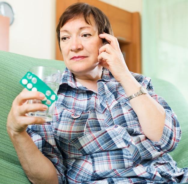 Mulher madura séria com pílulas e copo de água