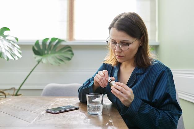 Mulher madura séria e triste com remédio, copo d'água e telefone