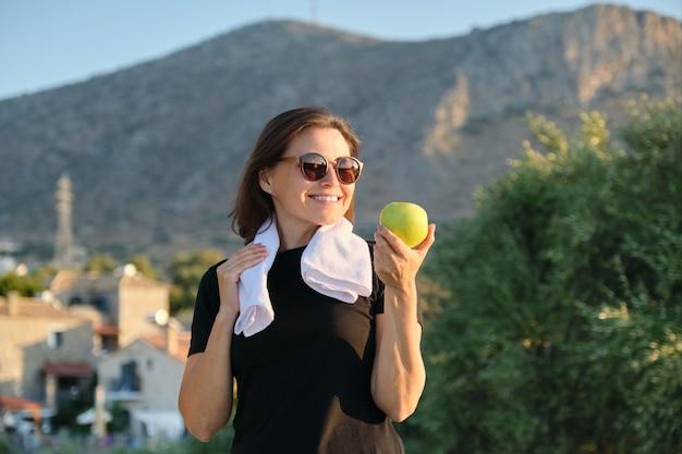 Mulher madura sorridente comendo maçã verde