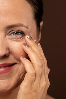 Mulher madura sorridente exibindo metade do rosto com maquiagem