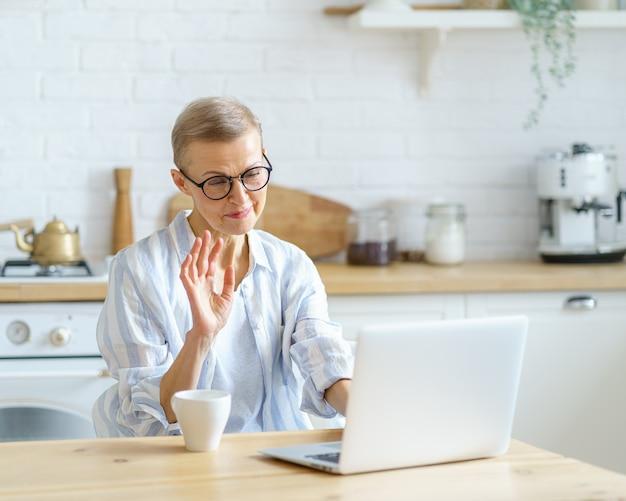 Mulher madura sorridente moderna usando óculos acenando para a webcam e estudando online no laptop enquanto