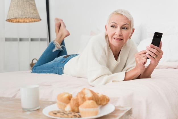 Mulher madura sorridente na cama segurando o smartphone