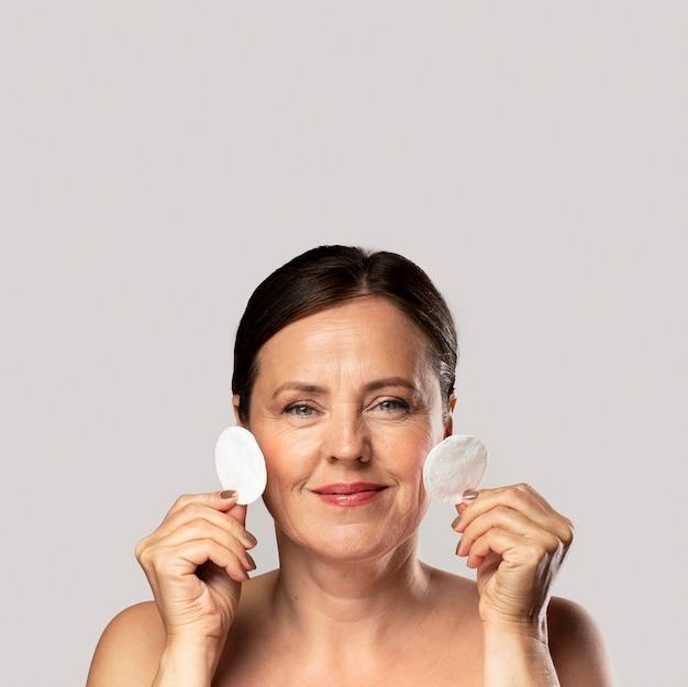 Mulher madura sorridente posando com almofadas de algodão para remoção de maquiagem e espaço de cópia