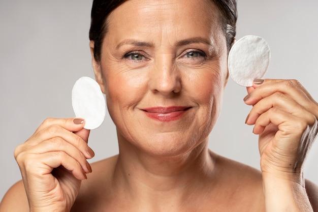 Mulher madura sorridente posando com almofadas de algodão para remoção de maquiagem