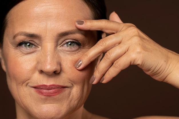 Mulher madura sorridente posando com maquiagem e mostrando as unhas