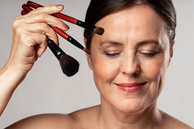 Mulher madura sorridente posando com pincéis de maquiagem