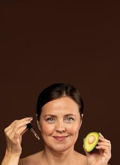 Mulher madura sorridente segurando metade de um abacate com soro e copie o espaço