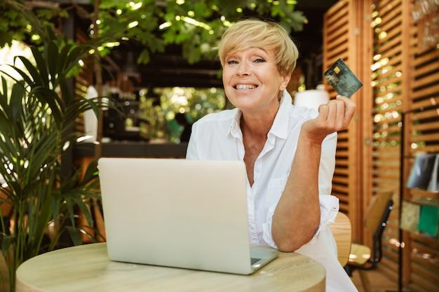 Mulher madura sorridente, sentado em um café com laptop