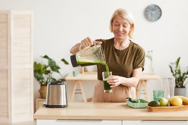 Mulher madura sorridente servindo coquetel de vegetais frescos no copo e bebendo