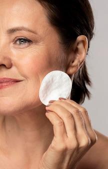 Mulher madura sorridente usando almofada de algodão para remoção de maquiagem