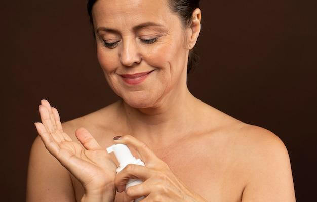Mulher madura sorridente usando limpador para o rosto