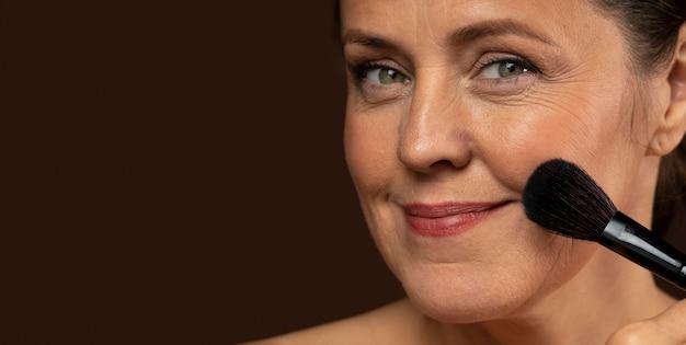 Mulher madura sorridente usando pincel de maquiagem no rosto com espaço de cópia