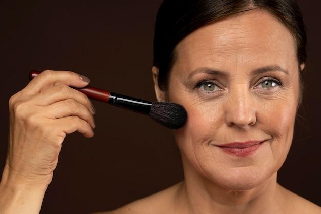 Mulher madura sorridente usando pincel de maquiagem no rosto